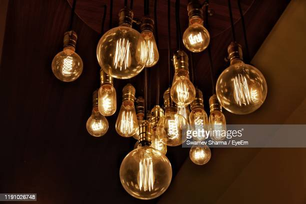 close-up of illuminated light bulb - pendant light stock pictures, royalty-free photos & images