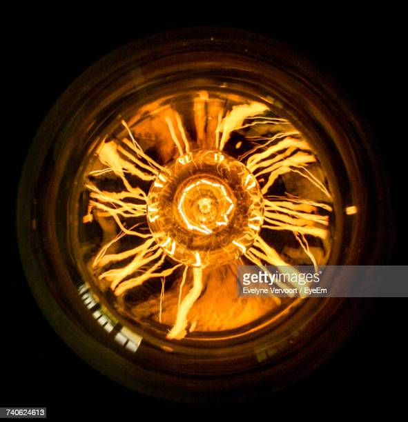 close-up of illuminated light bulb - filament stock photos and pictures