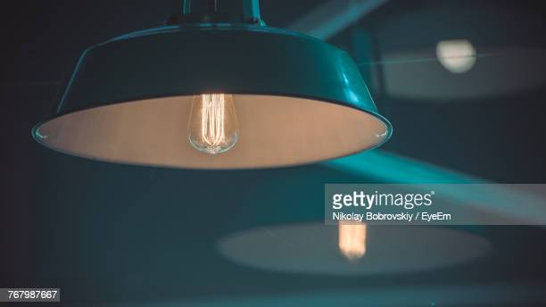 close-up of illuminated light bulb - electric lamp stock photos and pictures