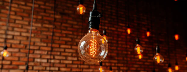 Close-up of illuminated light bulbs hanging against wall