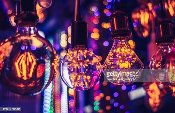 close-up of illuminated light bulbs hanging from ceiling - period bildbanksfoton och bilder