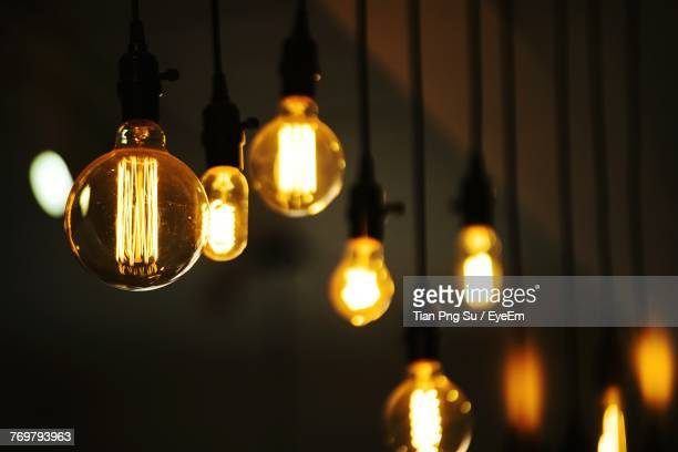 close-up of illuminated light bulbs hanging in darkroom - light bulb stock pictures, royalty-free photos & images