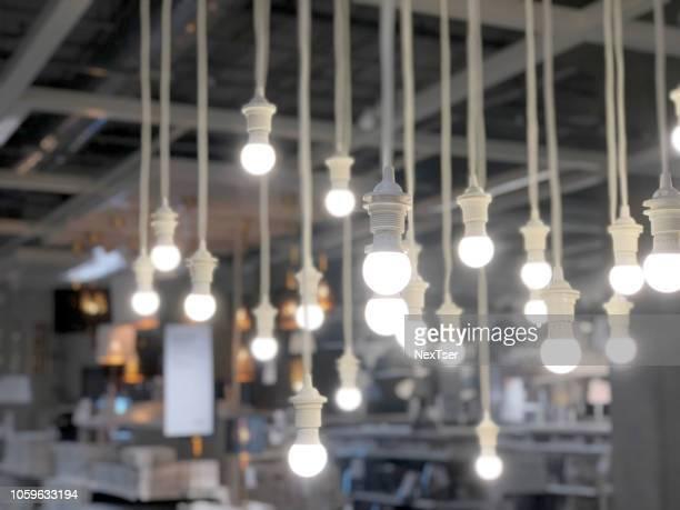 close-up of illuminated light bulbs hanging in store - accessorio per le lampade foto e immagini stock