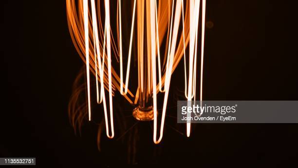 close-up of illuminated lighting equipment against black background - filament stock photos and pictures