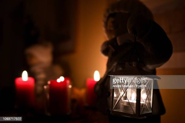 Close-Up Of Illuminated Lighting Equipment And Candles In Darkroom During Christmas
