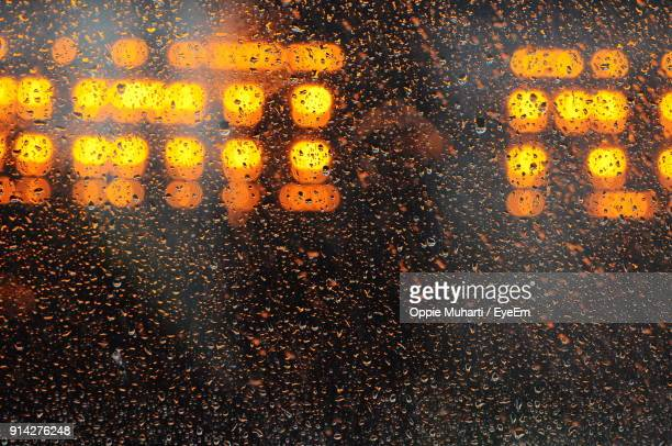 close-up of illuminated lights seen through wet glass - oppie muharti stock pictures, royalty-free photos & images