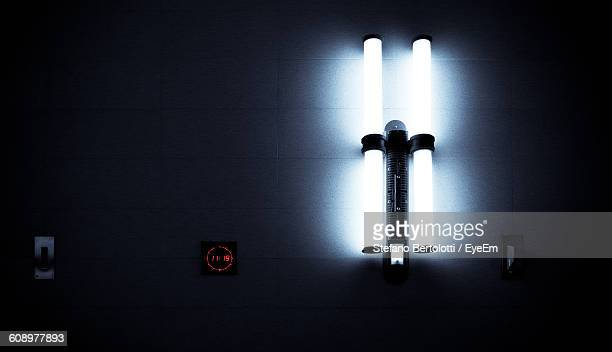 Close-Up Of Illuminated Neon Lights Mounted On Wall With Digital Clock