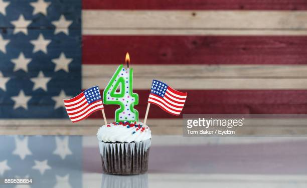close-up of illuminated number candle on cupcake against american flag - independence day holiday stock photos and pictures