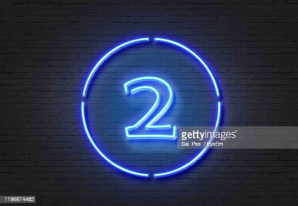 close-up of illuminated number on wall - number 2 stock pictures, royalty-free photos & images