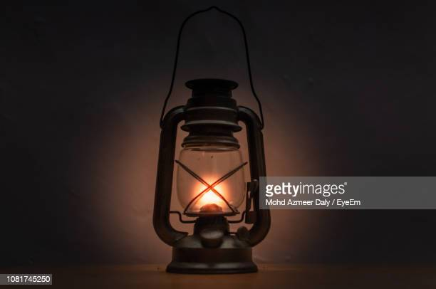 close-up of illuminated oil lamp against wall - oil lamp stock pictures, royalty-free photos & images