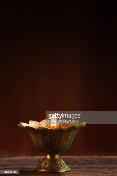close-up of illuminated oil lamp on table against wall - diwali decoration stock pictures, royalty-free photos & images