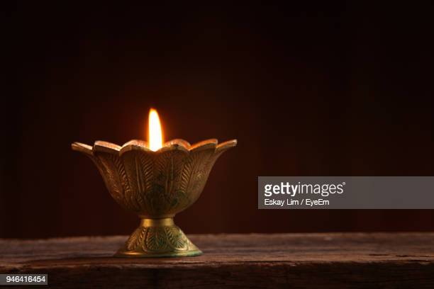 close-up of illuminated oil lamp on table against wall - diwali stock photos and pictures