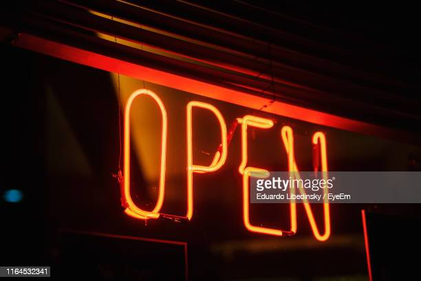 close-up of illuminated open text hanging in dark - open for business stock pictures, royalty-free photos & images