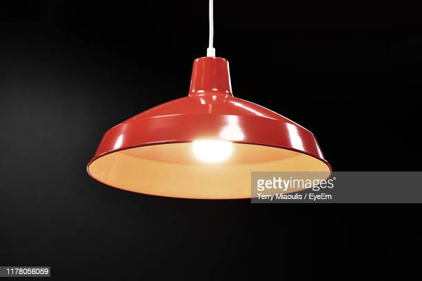 close-up of illuminated pendant light over black background - pendant light stock pictures, royalty-free photos & images