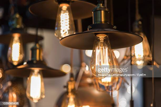 close-up of illuminated pendant lights hanging in restaurant - electric lamp stock photos and pictures