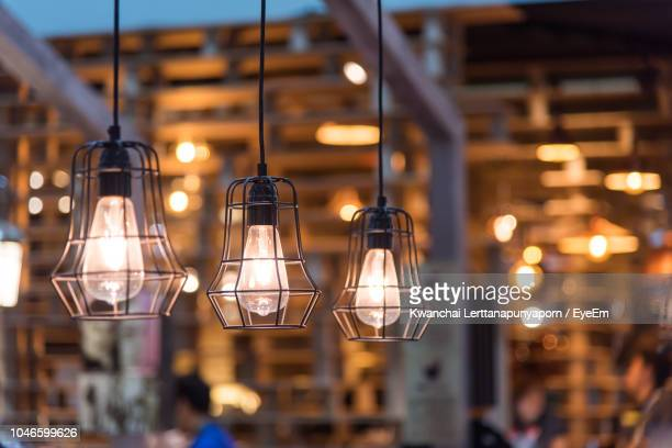 close-up of illuminated pendant lights hanging in restaurant - pendant light stock pictures, royalty-free photos & images