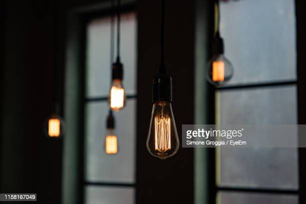 close-up of illuminated pendant lights in darkroom - pendant light stock pictures, royalty-free photos & images