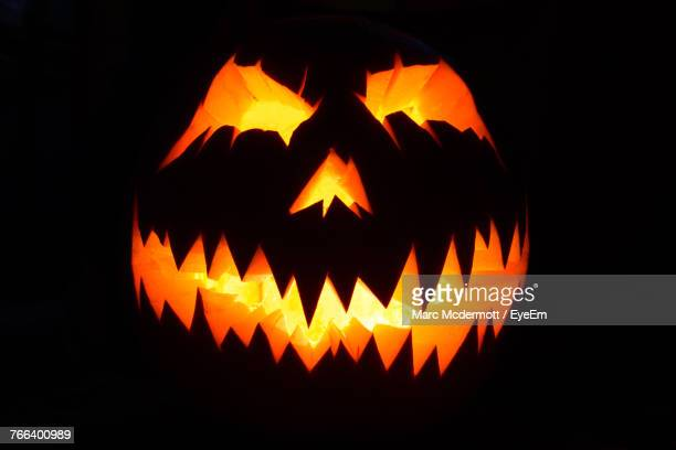 close-up of illuminated pumpkin against black background - scary pumpkin faces stock photos and pictures