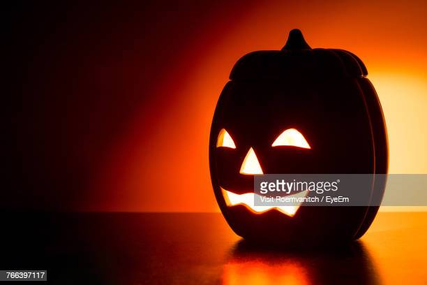 close-up of illuminated pumpkin on table - scary pumpkin faces stock photos and pictures