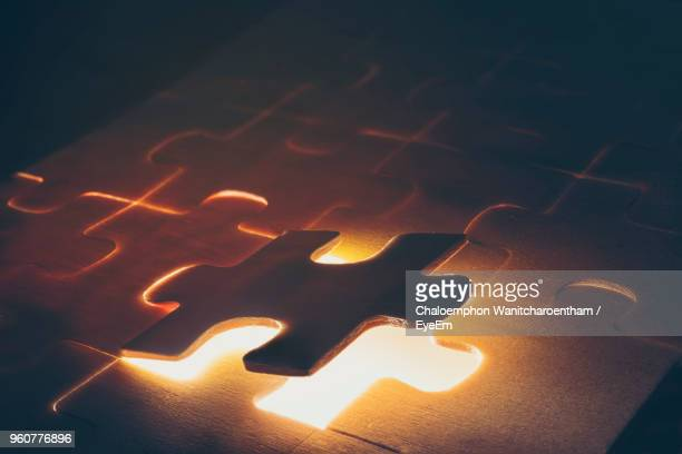 close-up of illuminated puzzle piece - jigsaw piece stock pictures, royalty-free photos & images