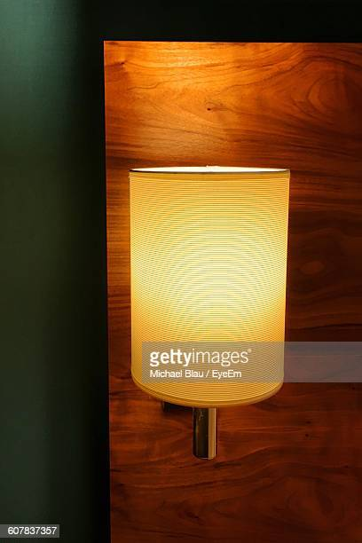 Close-Up Of Illuminated Sconce On Wooden Wall