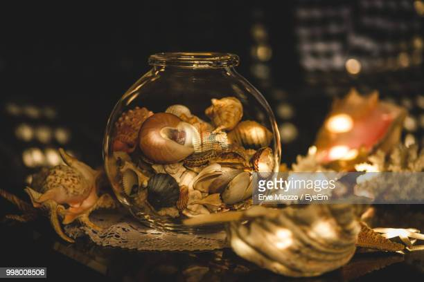 Close-Up Of Illuminated Shells In Glass Container On Table