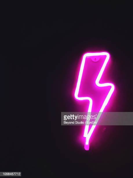 close-up of illuminated sign against black background - strom stock-fotos und bilder