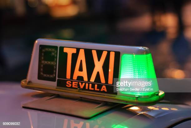 Close-Up Of Illuminated Sign On Taxi At Night