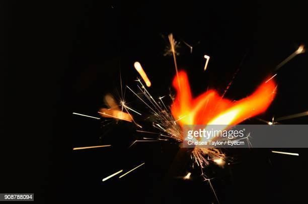 close-up of illuminated sparkler against black background - sparks stock pictures, royalty-free photos & images