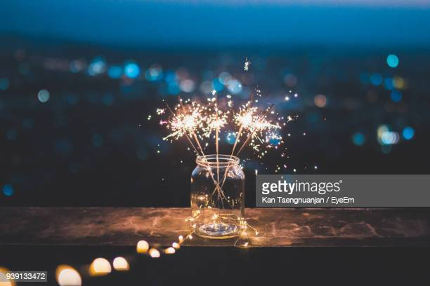 close-up of illuminated sparkles in jar on retaining wall - festeggiamento foto e immagini stock