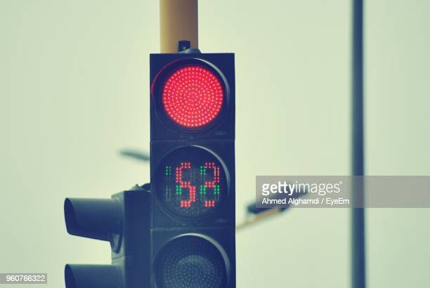 close-up of illuminated stoplight against clear sky - red light stock pictures, royalty-free photos & images