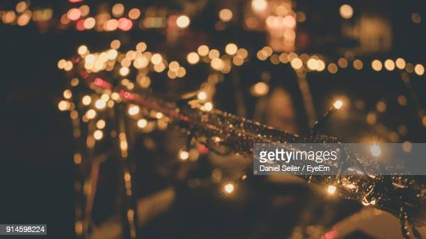 close-up of illuminated string lights at night - christmas scenes stock photos and pictures