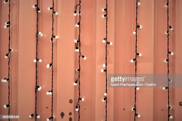 Close-Up Of Illuminated String Lights Hanging Against Wall