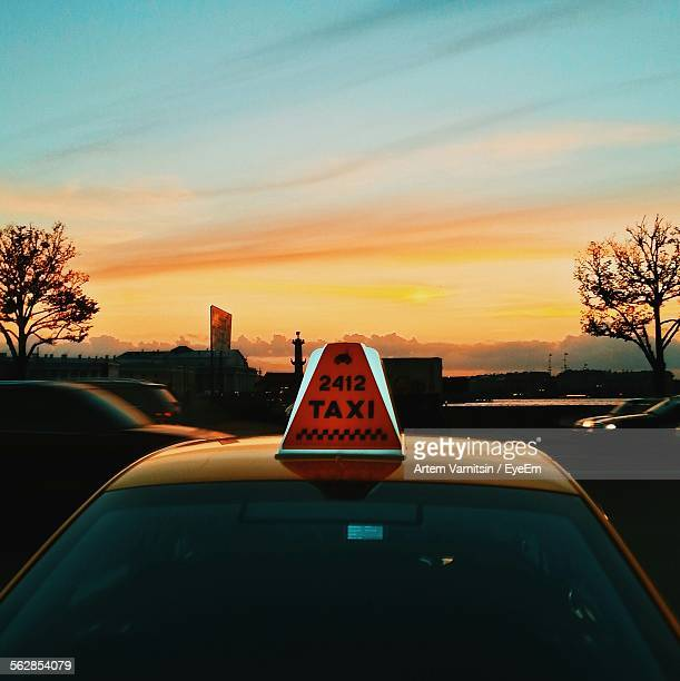Close-Up Of Illuminated Taxi Sign On Vehicle Roof Against Sky At Dusk