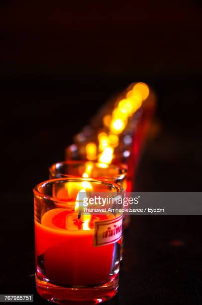 Close-Up Of Illuminated Tea Light Candle On Table In Darkroom