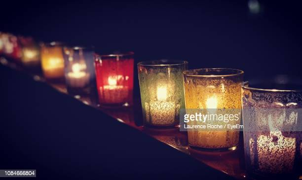 Close-Up Of Illuminated Tea Light Candles On Table