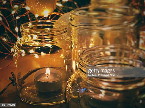 close-up of illuminated tea light candles on table - nathalie pellenkoft stock pictures, royalty-free photos & images