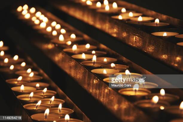 close-up of illuminated tea lights in dark - greek orthodoxy stock pictures, royalty-free photos & images