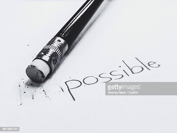 close-up of impossible text on white paper with pencil - eraser stock pictures, royalty-free photos & images