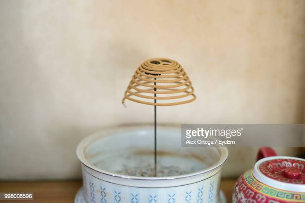 Close-Up Of Incense Burning Against Wall