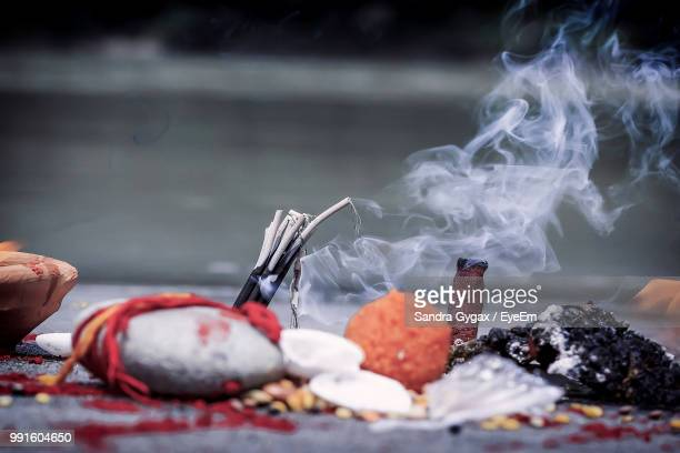 close-up of incense emitting smoke by religious offering - sandra gygax stock-fotos und bilder