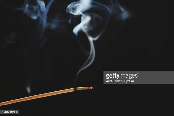 close-up of incense stick against black background - incense stock photos and pictures