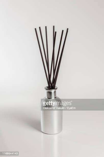 close-up of incense sticks in metallic container against gray background - incense stock pictures, royalty-free photos & images