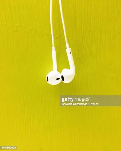 Close-Up Of In-Ear Headphones Hanging By Yellow Wall