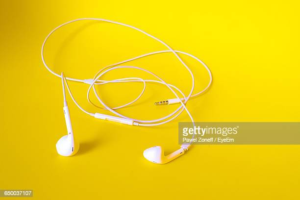 Close-Up Of In-Ear Headphones On Yellow Background
