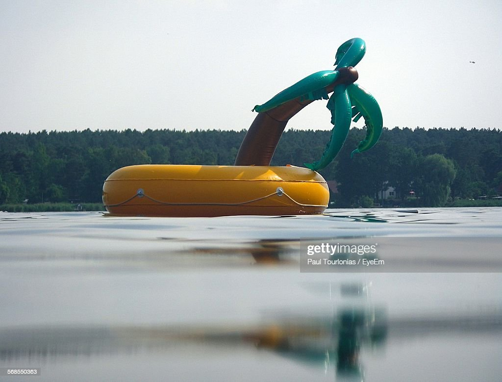 Close-Up Of Inflated Toy Floating On Lake Against Sky : Stock Photo