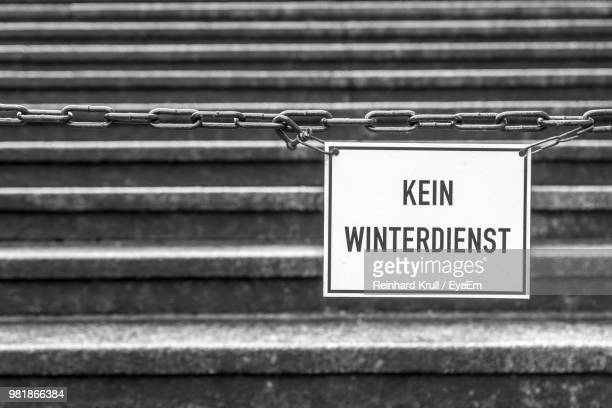 Close-Up Of Information Sign Hanging On Chains Against Steps