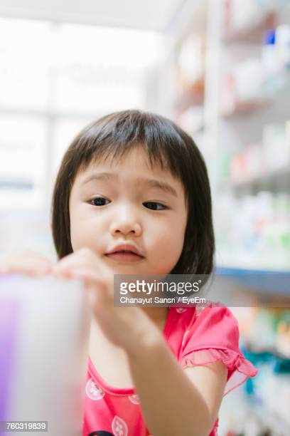 close-up of innocent girl standing in store - chanayut stock photos and pictures