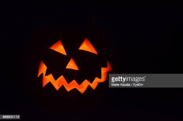close-up of jack o lantern against black background - halloween pumpkin stock photos and pictures