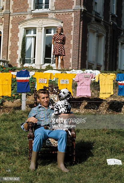 CloseUp Of Jacques Anquetil En France en 1969 Jacques ANQUETIL en jean et bottes assis dans un fauteuil tenant son chien dalmatien sur ses genoux en...